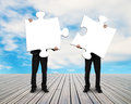 Two men holding puzzles on wooden floor Royalty Free Stock Photo