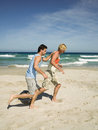 Two men jogging on the beach sandy Stock Photo