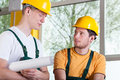 Two men in overalls and hardhat during work young talking Stock Photography