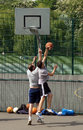 Two men playing outdoor basketball play in the playground of clissold park london Royalty Free Stock Photos