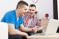 Two men pointing at laptop the best male friends spending time together with Stock Photo