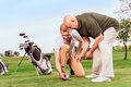 Two men putting ball on tee at course Royalty Free Stock Photo