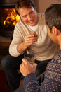 Two Men Relaxing Sitting On Sofa Drinking Whisky Royalty Free Stock Photo