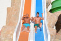 Two men riding down a water slide-friends enjoying a water tube ride Royalty Free Stock Photo