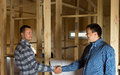 Two men shaking hands in a half constructed house timber frame with building blueprint alongside them as they signal their Stock Images
