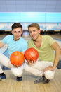 Two men sit on floor with balls in bowling club Stock Photo