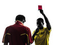 Two men soccer player and referee showing red card silhouette in on white background Stock Photography