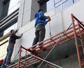 Two men stand on scaffolding and work exterior repairs the building in downtown amoy city china Stock Photo