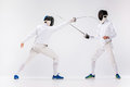 The two men wearing fencing suit practicing with sword against gray Royalty Free Stock Photo