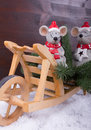 Two mice take a break on a wheelbarrow with fir trees snow and dark colored wooden rustic background Stock Images