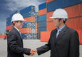 Two of Mid adult businessman shaking hands  near cargo container Royalty Free Stock Photo