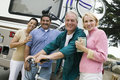 Two middle aged couples standing beside caravan Stock Image