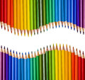 Two mirrored waves of colorful pencils on white Stock Image
