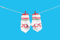 Two mittens isolated on blue background and heart clothesline with clothespins Stock Images