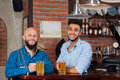 Two Mix Race Man In Bar Hold Glasses Sit At Counter, Drinking Beer, Cheerful Friends Meeting Royalty Free Stock Photo