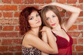 Two models pose, hug near brick wall Stock Photos