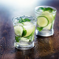 Two mojito cocktails on wet wooden table Royalty Free Stock Images