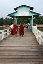 Two monks walking on U-Bein Bridge in Amarapura Stock Image