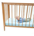 Two months baby boy lying in a crib Royalty Free Stock Image