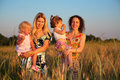 Two mothers with children on wheaten field Royalty Free Stock Photo