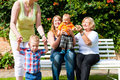 Two mothers with grandmother and children in park Royalty Free Stock Photo