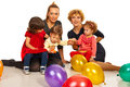 Two mothers with kids their at party balloons sitting on floor together Stock Photography
