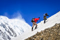 Two mountain trekkers on snow with peaks background backpackers walking himalayas Stock Photos