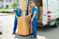 Two movers loading boxes in truck happy blue uniform Stock Images