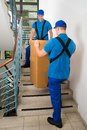 Two movers standing with box on staircase male in uniform Royalty Free Stock Photo