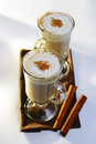 Two mugs of frothy hot chocolate with cinnamon on a rustic wooden tray spicy dried sticks high angle view the Royalty Free Stock Photos