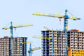 Two multi-storey buildings under construction. Many cranes. Construction of modern housing. Royalty Free Stock Photo