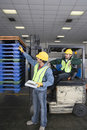 Two multiethnic men working in factory side view of young Royalty Free Stock Images