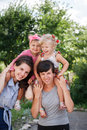 Two mums with their kids giving piggyback rides outdoors Stock Image