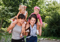 Two mums with their kids giving piggyback rides outdoors Stock Photos