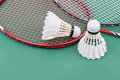 Two new badminton shuttlecock with rackets on green mat court Royalty Free Stock Photo