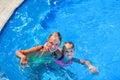 Two nice children girl swim in swimming pool.