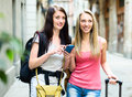 Two nice girls finding path with GPS navigator Royalty Free Stock Photo