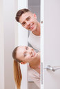 Two nice persons emerge from behind door here we are cheerful people white Royalty Free Stock Image
