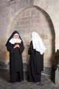 Two nuns in an old convent young passing eachother a medieval this is a composite only model release needed Stock Image