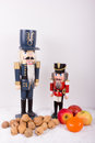 Two nutcracker with nuts as a christmas decoration and snow and fruits in the foreground Royalty Free Stock Photo