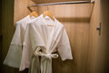 Two off white color bathrobes hanging in warmly design closet, r Royalty Free Stock Photo