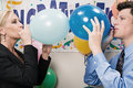 Two office workers blowing up balloons Royalty Free Stock Photo