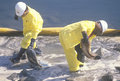 Two oil cleanup workers wade in oily water between a yellow oil barrier and a rocky shoreline clearing up oil with absorbent mater