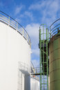 Two oil tanks white and green diesel of a refinery under a blue sky Stock Photography