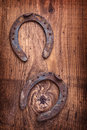 Two old rusted horsehoes on vintage wooden board Royalty Free Stock Photo