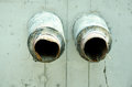 Two old sewage or water pipes exit from concrete block in the ground. Royalty Free Stock Photo