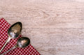 Two old silver spoons on checkered cloth and weahtered wood Royalty Free Stock Photography