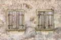 Two old windows with closed shutters gray weathered window in the run down gray facade of an abandoned house Royalty Free Stock Photos