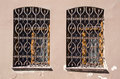 Two old windows with metal gratings Royalty Free Stock Photo