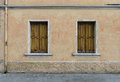 Two old windows with shutters in the old scratched wall, Palmanova Royalty Free Stock Photo